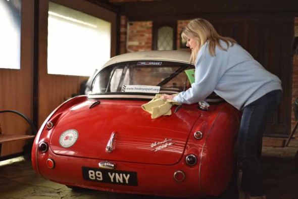 Image of woman cleaning red classic car