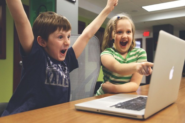 Two excited children looking at successful A/B test on laptop