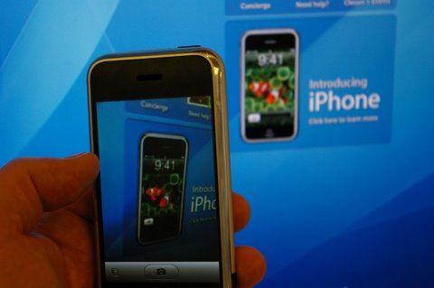 Image of the first iPhone in front of an advert for the iPhone
